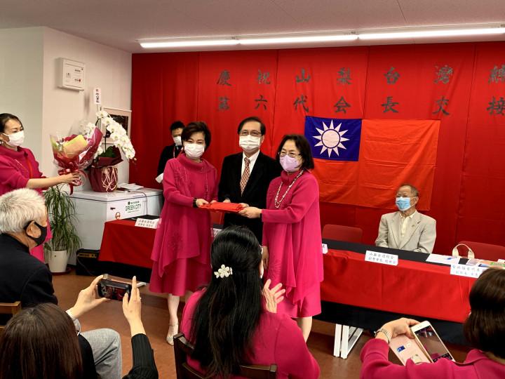 在駐日本代表處僑務組組長謝延淙(中)見證下第五屆會長黃碧霞(右)將印信交給第六屆會長孫亞彤(左)