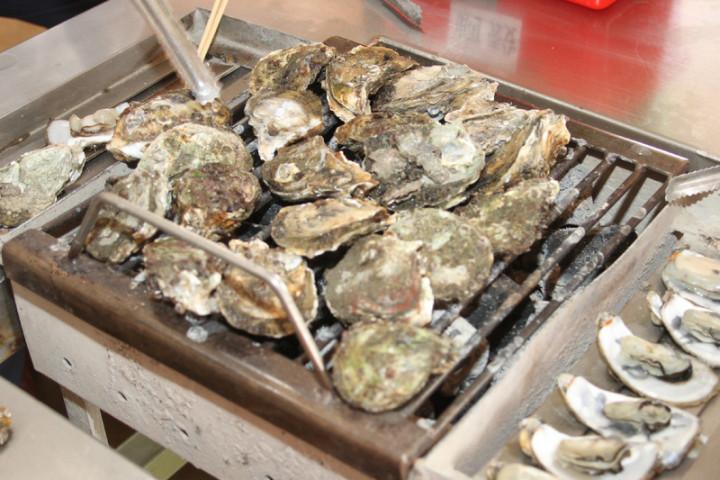 牡蠣是許多民眾喜愛的食材,但近日受防疫措施影響,市場需求下滑,台南近海放養蚵棚又遭風浪毀損,農民損失不小。圖為帶殼烤牡蠣。