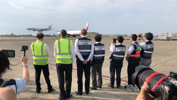 Officials including AIT Director Brent Christensen and Health Minister Chen Shih-chung watch the landing of the China Airlines plane that carries the COVID-19 vaccine donated from the U.S.
