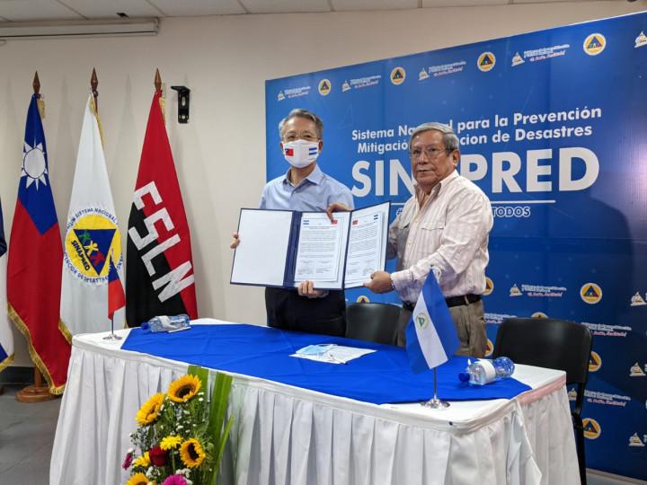 大使吳進木與署長Guillermo González展示捐贈記事錄