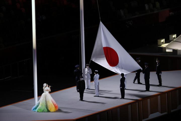 因疫情延後一年舉行的東京奧運,23日晚間在日本新宿國立競技場舉行開幕式,主辦國日本的國旗也在場內緩緩升起。歌手米希亞(左1)演唱日本國歌。
