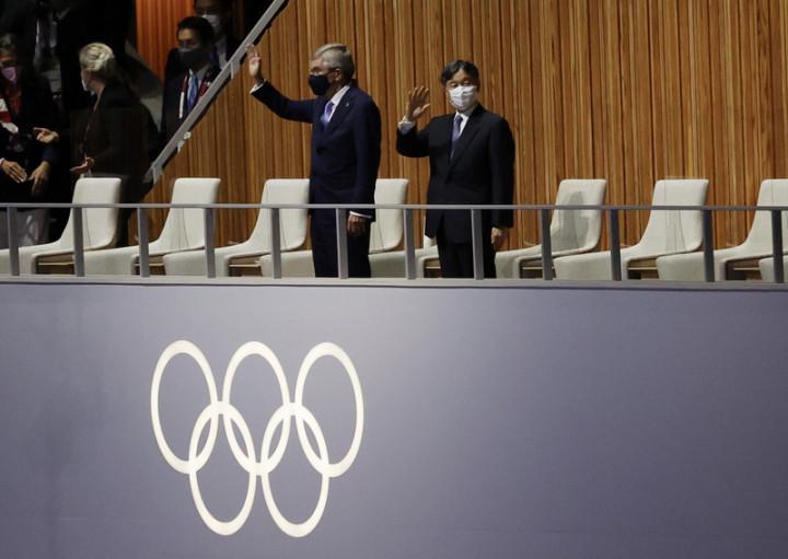 因疫情延後1年舉行的東京奧運,23日晚間在日本新宿國立競技場舉行開幕式,日本天皇德仁(右)及國際奧會(IOC)主席巴赫(Thomas Bach)(右2)出席,揮手致意。