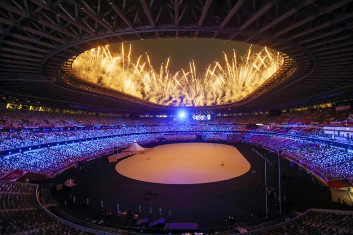 東京奧運23日晚間在日本新宿國立競技場舉行開幕式,受疫情影響本屆典禮並未開放觀眾進入場內,但現場表演仍照常舉行,璀璨煙火自場館高處噴發,點亮夜空。