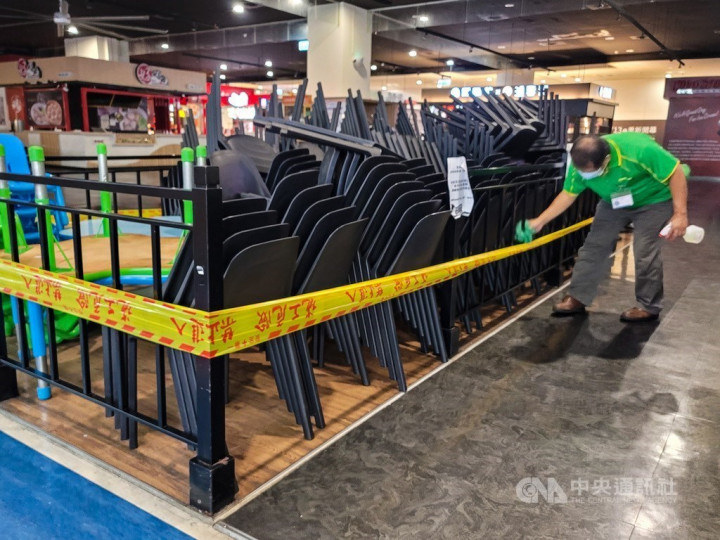 A shopping mall worker disinfects stacks of chairs at a food court in Taipei on Friday. CNA photo July 23, 2021