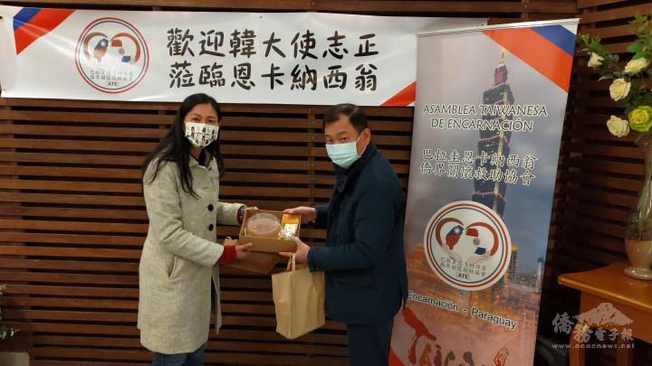 恩卡協會孫冰君副會長(左)向到訪的韓志正大使(右),送上恩市僑胞手作的臺式鳳梨酥伴手禮。