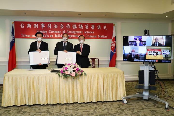 外交部吳部長(左)、博塔文代表(左二)及法務部蔡部長(左三)手持簽署完成的協議,與觀禮斯國政要及我駐斯國李代表合影留念。