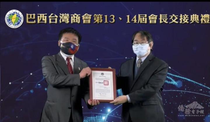 劉俊男主任(右)頒僑委會委員長童振源賀函予新任會長蔡逢興(左)