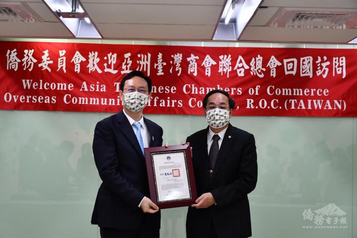 童振源(左)頒發賀狀給新任亞洲臺灣商會聯合總會總會長江福龍(右)