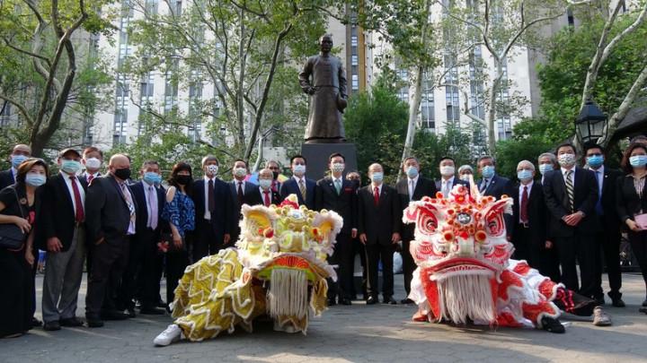 僑委會委員長童振源(銅像下方綠色領帶者)13日拜訪紐約曼哈頓華埠,在哥倫布公園中山廣場與國父孫中山銅像合影。