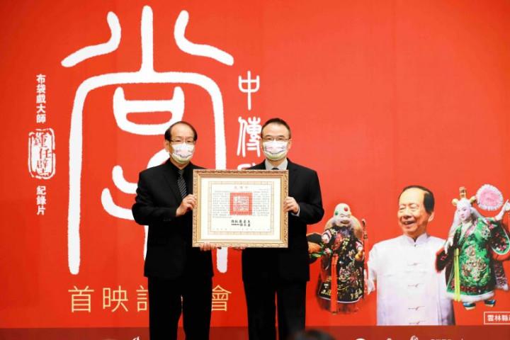 文化部政務次長蕭宗煌(右)代表頒贈總統褒揚令,由鍾任壁藝師之子新興閣第六代傳人鍾任樑代表受贈
