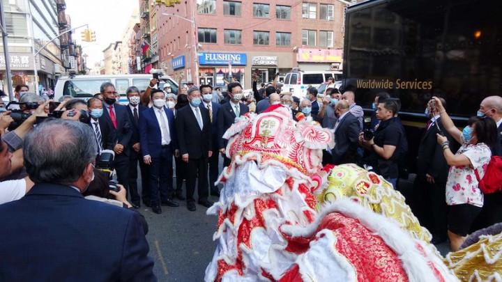 僑委會委員長童振源(綠色領帶者)13日拜訪紐約曼哈頓華埠,僑界人士在勿街路口迎接,並獻上舞獅表演。