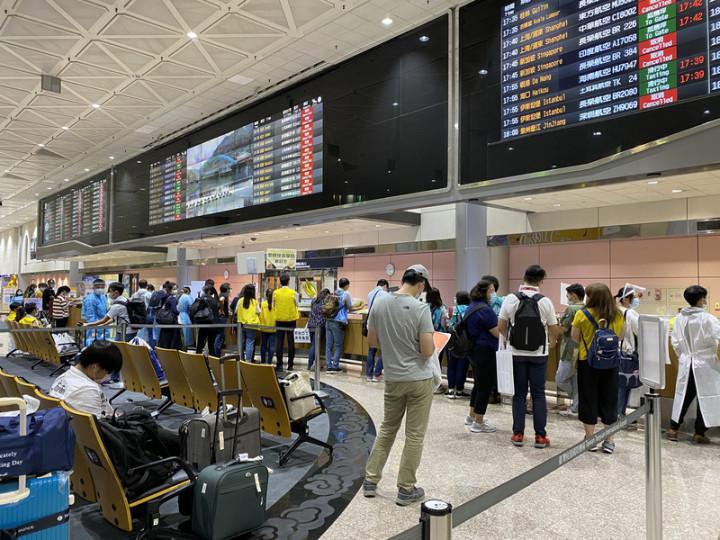 在政府宣布開放境外生入境後,各大專防疫人員肩負 起境外生入境的檢疫和安置等事務,人員在機場大廳高舉學校名牌,等候境外生入境。(許慈芳提供)