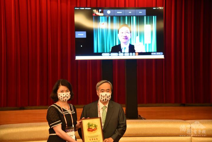 梁輝騰 (右)贈送感謝狀予童振源,由僑商處處長張淑燕(左)代表受贈