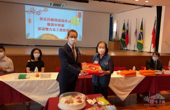 馮光中贈送月餅給與會志工,由惠榮譽班長江美代表接受