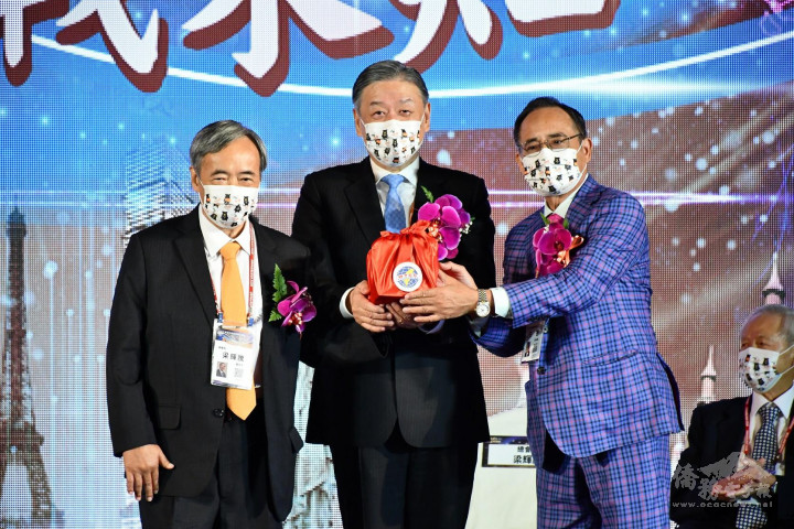在僑委會副委員長呂元榮(中)監交下,世總27屆總會長梁輝騰(左)將印信交接給28屆總會長王德(右)。