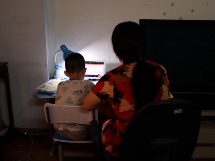 因為COVID-19疫情,越南的小學生2021年幾乎都在家線上學習,家長在工作之餘又要花時間陪小孩上課,長久下來疲憊不堪。圖為正在陪課的越南家長。