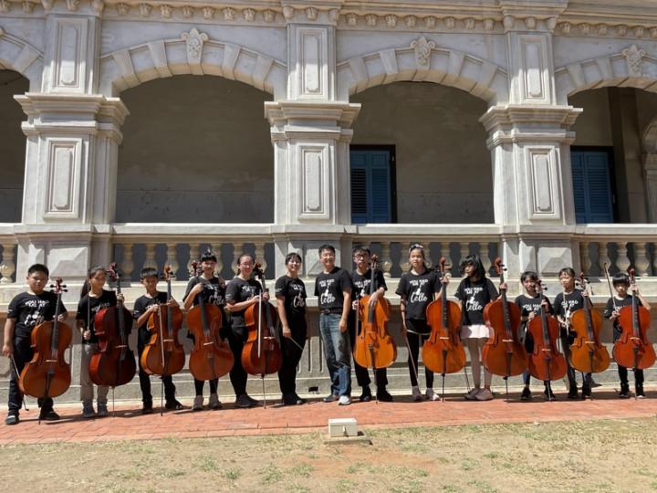 金門縣金沙鎮述美國小校長劉界宏(中)鑑於學校地處偏遠,學生藝文刺激低,與留學法國的老師陳怡潔(左6)成立大提琴團等音樂性社團,幫助學生能自小培養一項樂器專長。