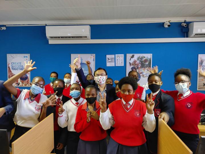 10月11日是國際女童日,駐南非代表處12日捐贈卜姆蘭尼中學女學生衛生用品,讓她們不會因為家貧被迫在生理期間缺課。圖為駐南非代表賀忠義(中著西裝外套者)與女學生合影。(駐南非代表處提供)