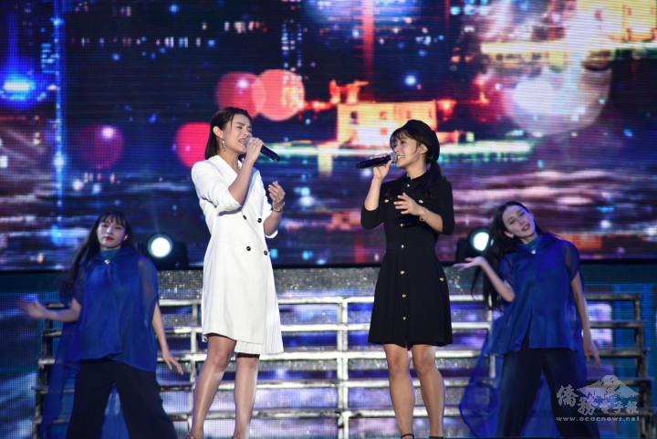 獲得「110年全球僑校學生暨僑生華語歌唱大賽」冠軍的馬來西亞僑生尤嘉綝(右)登上國慶晚會演出