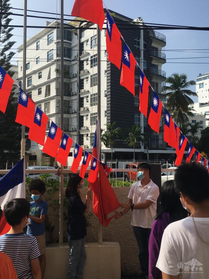 由中文學校學生手持中華民國國旗與多明尼加國旗預備升旗