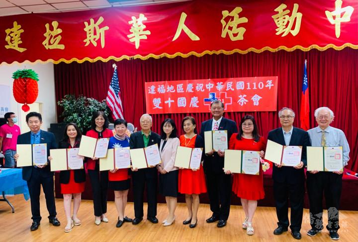 黃依莉(中)代表僑務委員會委員長童振源頒發僑務榮譽職人員聘書予僑務諮詢委員孟敏寬(左4)等僑領。