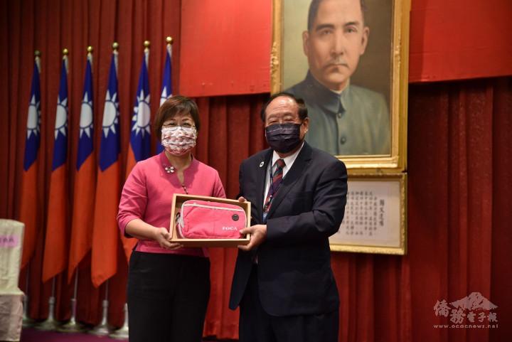徐佳青(左)自鄭致毅(右)手中接下紀念品。