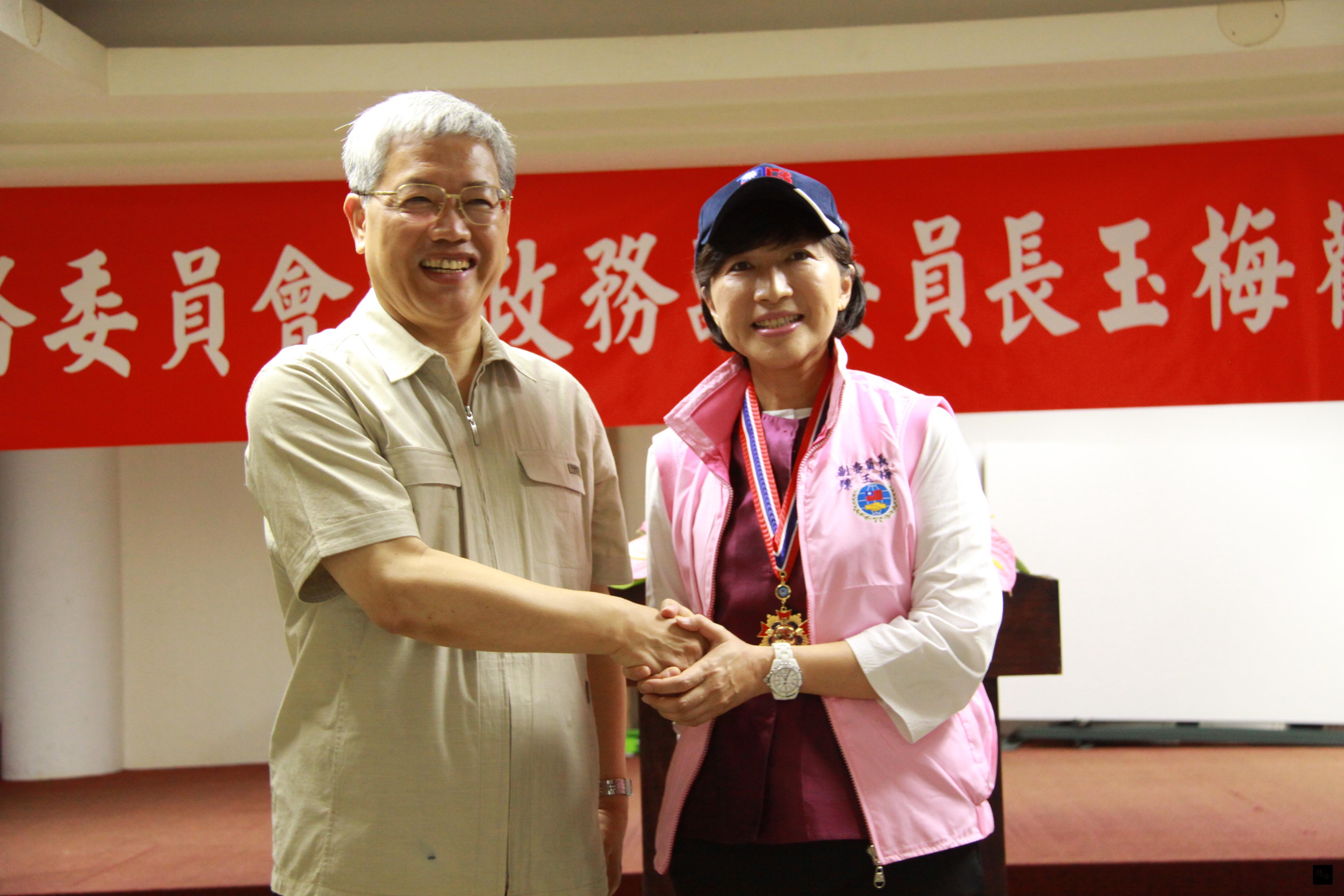 僑委會委員長陳士魁(左)致贈志工帽及志工背心給副委員長陳玉梅(右),希望她能夠做永遠的僑務志工。