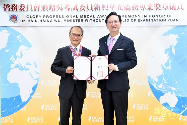童振源(右)頒發華光僑務專業獎章予吳新興(左)。