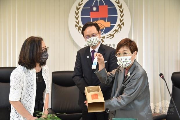 由童振源(中)、徐佳青(右)代表僑委會致贈劉淑慧(左) 鳳梨酵素防疫洗手液。