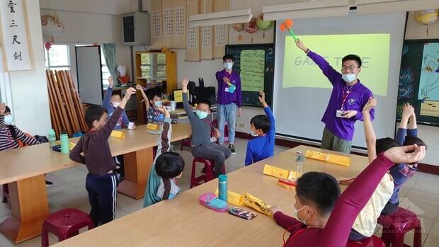 2021年海外青年英語服務營輔導員親切教導國小學童。