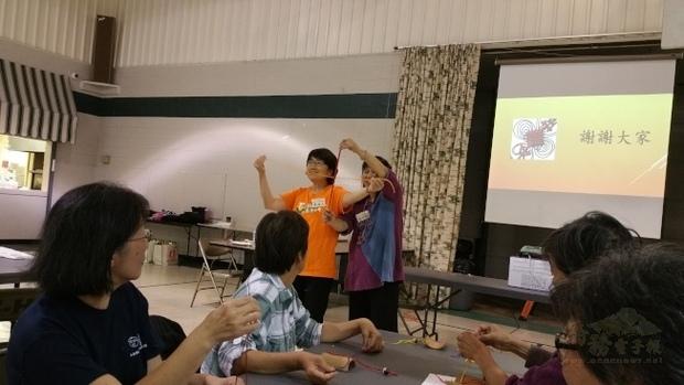 「海外民俗文化種子教師在地研習」覃潔人(左立者)與張淑娟(右立者)展示十字結的基本打法。(世界日報提供)