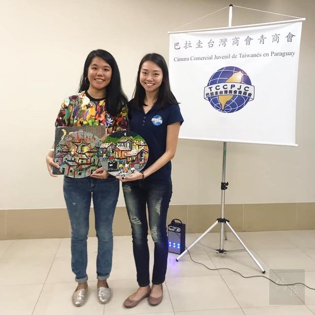 約克(左)帶來了她在「大社區」購買的紀念畫作,致贈給青商會,會長劉倩如(右)代表接受。