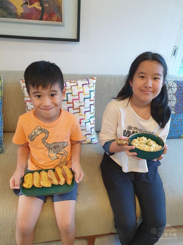菲華文經總會兒童線上烹飪班學員鍾鈺明(左)與鍾雪真(右)展示烹煮好的芝士通心粉與大蒜麵包。