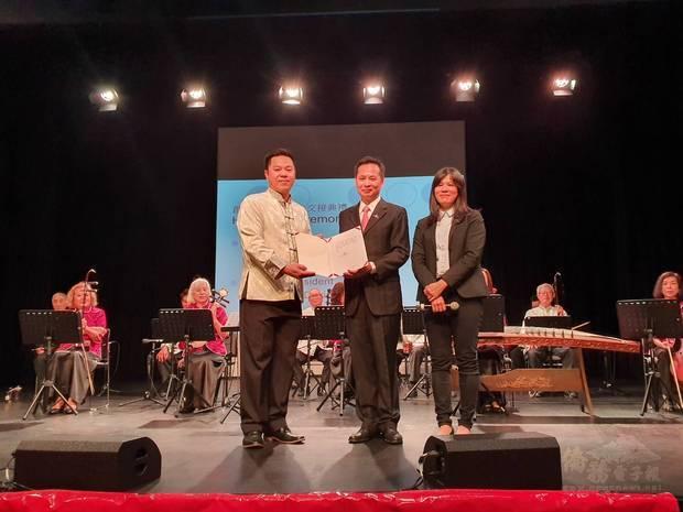 洪振榮代表頒發吳新興賀函予新任會長劉正偉(右)。
