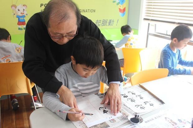 黃振鍹老師指導學生習寫書法。