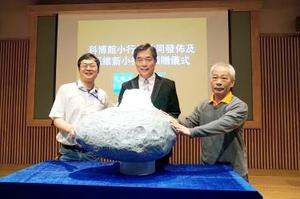National Museum of Natural Science Director-General Sun Wei-hsin, center, Lulin Observatory director Lin Hung-chin, left, and observatory assistant Lin Chi-sheng pose with a model of an asteroid at a ceremony at the museum in Taichung yesterday./Phot