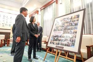President Tsai Ing-wen, second left, and Minister of Health and Welfare Chen Shih-chung, left, look at photographs at the Ministry of Health and Welfare yesterday that show the Taiwanese delegation's visit to the ongoing World Health Assembly in Gene