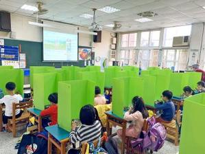 Pupils at the Chienkung Elementary School in Hsinchu yesterday eat lunch separated by isolation panels fashioned by their teacher as part of disease-prevention measures./Photo courtesy of Taipei Times