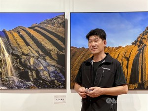Taiwanese photographer Lee Ming-tsung (李明宗) stands besides his works exhibited at National Dr. Sun Yat-sen Memorial Hall in Taipei / Photo courtesy of CNA