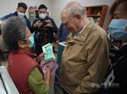 An 83-year-old woman makes a NT$800 donation during a meeting with Father Giuseppe Didone. / Photo courtesy of CNA