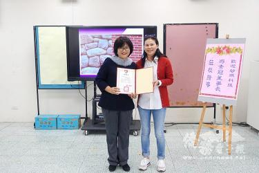 Businesswoman Yu Su-kuan, right, holds an award presented by Chungher Elementary School principal Liu Wen-chi in Keelung on Saturday./Photo courtesy of Taipei Times