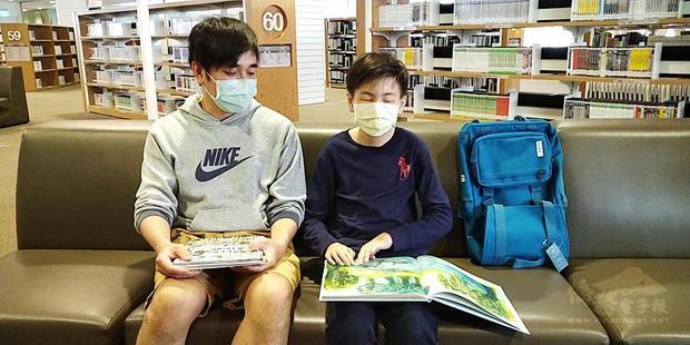 Wu Ching-yu, right, accompanied by his father, reads a book at the Kaohsiung Main Public Library on Friday. / Photo courtesy of Taipei Times