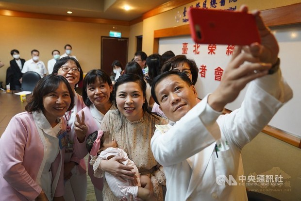 Le Van Dai Trang, carrying her baby daughter, poses for a group selfie with the medical staff at Taipei Veterans General Hospital on Monday /Photo courtesy of CNA