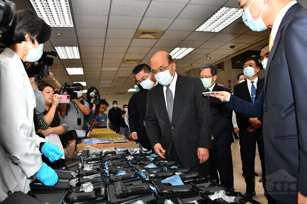 Premier Su Tseng-chang (center) applauds the Criminal Investigation Bureau for the largest seizure of illegal ammunition in Taiwan's history.