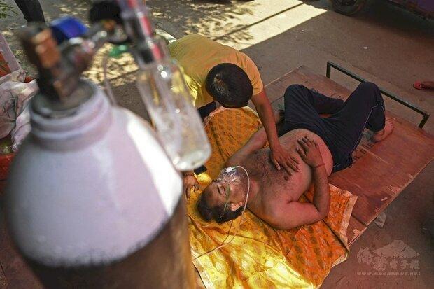 印度第二波疫情不斷升溫導致醫療系統崩潰。圖為染疫民眾在醫院外接受供氧。